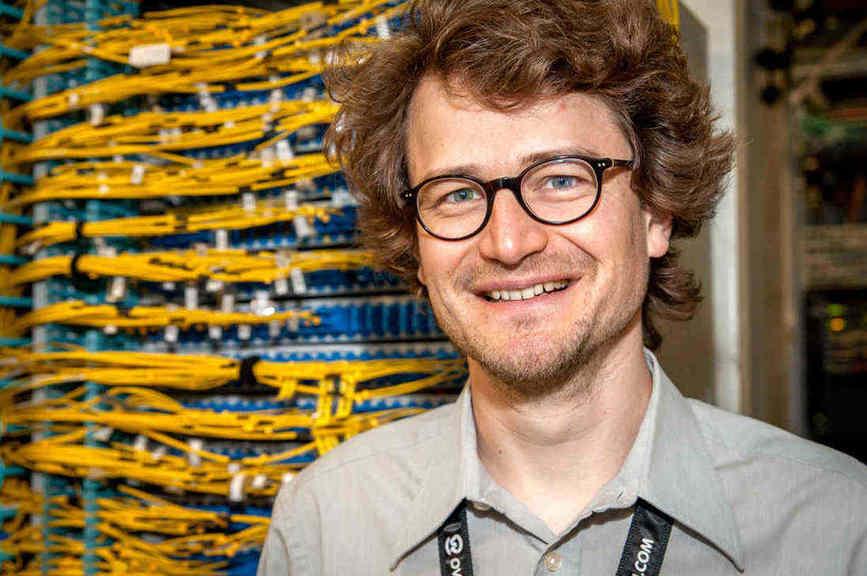 Guillaume Delabre, administrateur réseau chez OVH, devant une baie de brassage de fibres du réseau privé vRack.